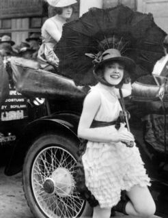 Parade of bathing beauties in Los Angeles in about 1921 with advertisement for Schlank costumes in background.