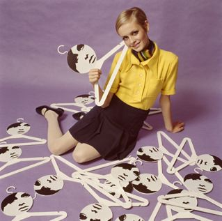 Leslie Hornby (aka Twiggy) posing with her portrait hangers, one of which was included with each purchase of a Twiggy dress, 1967