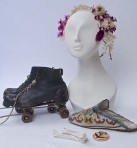 Clockwise from bottom: White boot laces, c. 1910s; Roller skates, 1908, 1860s headpiece; 1879 petit point slipper; Vietnam era pinback