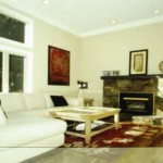 Living room with a smaller fireplace and coving...