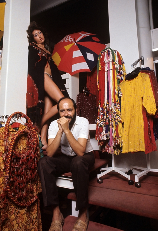 Italian fashion designer and entrepreneur Elio Fiorucci posing in his shop in Galleria Passarella. In the background, the shop assistant Cristina Bagnoli posing wearing a sexy gown designed by the fashion designer. Milan, 1970 (Photo by Giuseppe Pino/Mondadori Portfolio via Getty Images)