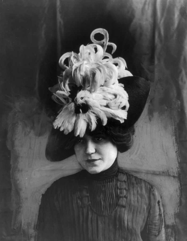"""Woman wearing a """"Chanticleer"""" hat (rooster feathers), circa 1912."""